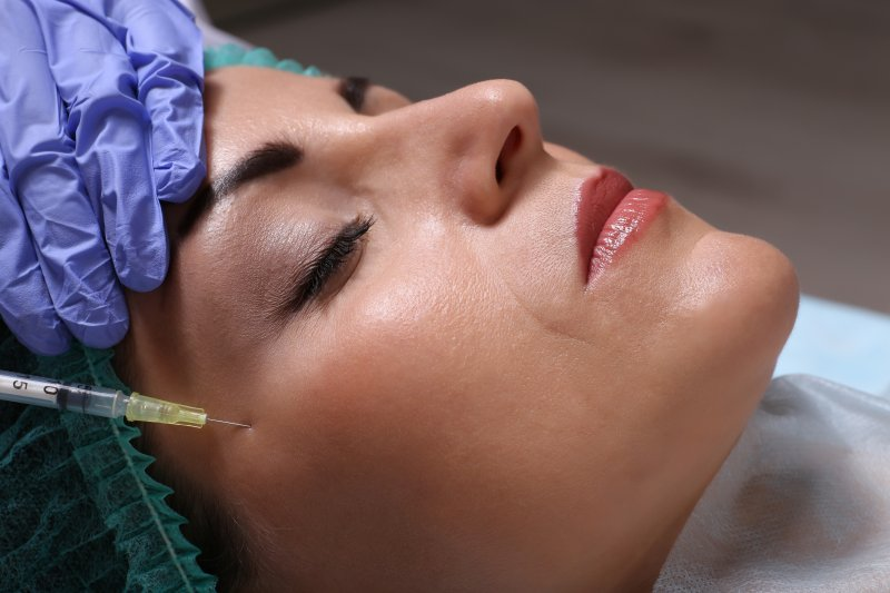 a middle-aged woman receiving dermal fillers during an appointment