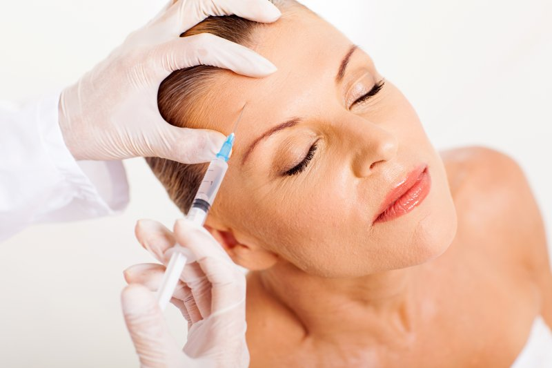 an older woman having BOTOX injected into her forehead