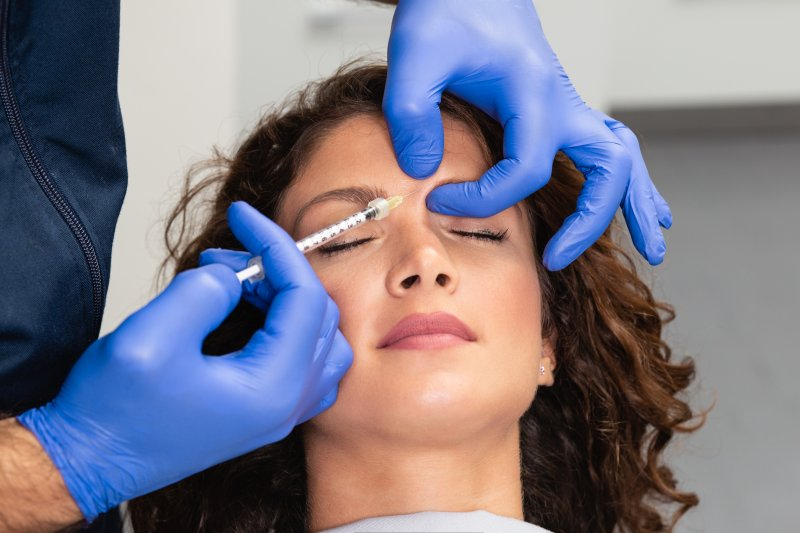 a patient having a Botox injection between her eyebrows